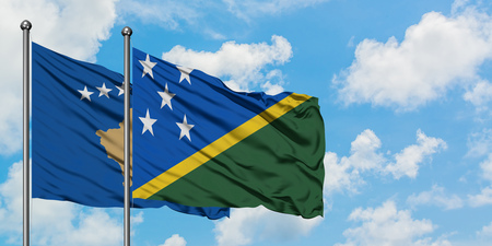Kosovo and Solomon Islands flag waving in the wind against white cloudy blue sky together. Diplomacy concept, international relations. Stok Fotoğraf
