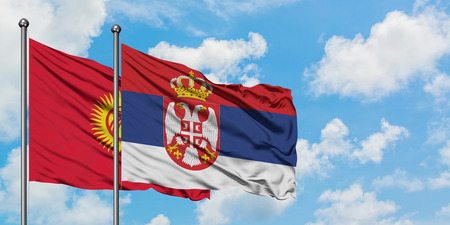 Kyrgyzstan and Serbia flag waving in the wind against white cloudy blue sky together. Diplomacy concept, international relations. Banque d'images