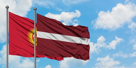 Kyrgyzstan and Latvia flag waving in the wind against white cloudy blue sky together. Diplomacy concept, international relations.