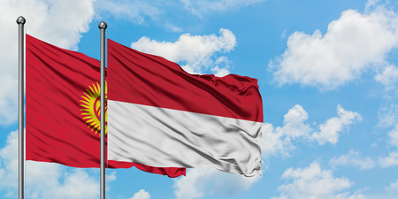 Kyrgyzstan and Indonesia flag waving in the wind against white cloudy blue sky together. Diplomacy concept, international relations.
