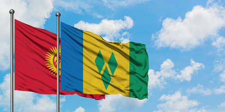 Kyrgyzstan and Saint Vincent And The Grenadines flag waving in the wind against white cloudy blue sky together. Diplomacy concept, international relations.