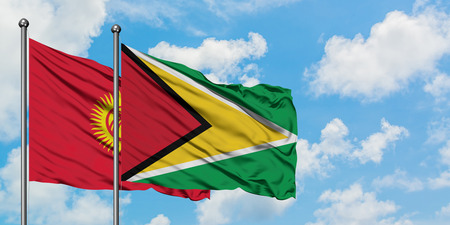 Kyrgyzstan and Guyana flag waving in the wind against white cloudy blue sky together. Diplomacy concept, international relations. Banque d'images