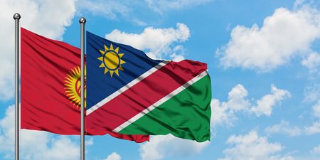 Kyrgyzstan and Namibia flag waving in the wind against white cloudy blue sky together. Diplomacy concept, international relations.