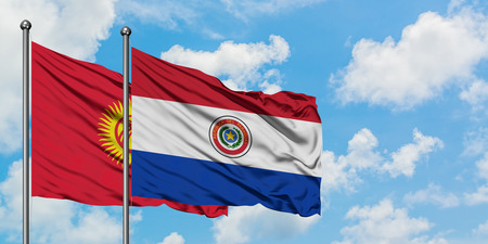 Kyrgyzstan and Paraguay flag waving in the wind against white cloudy blue sky together. Diplomacy concept, international relations.
