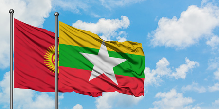 Kyrgyzstan and Myanmar flag waving in the wind against white cloudy blue sky together. Diplomacy concept, international relations.