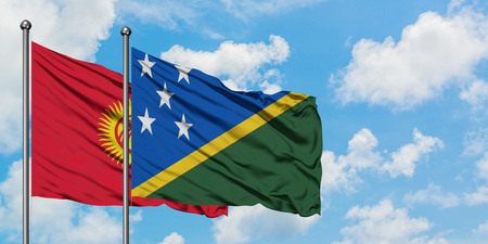 Kyrgyzstan and Solomon Islands flag waving in the wind against white cloudy blue sky together. Diplomacy concept, international relations.
