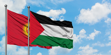 Kyrgyzstan and Palestine flag waving in the wind against white cloudy blue sky together. Diplomacy concept, international relations.