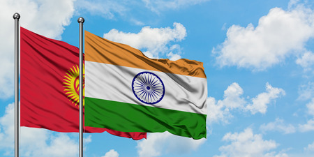 Kyrgyzstan and India flag waving in the wind against white cloudy blue sky together. Diplomacy concept, international relations.