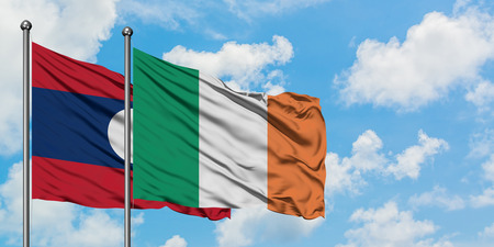 Laos and Ireland flag waving in the wind against white cloudy blue sky together. Diplomacy concept, international relations. Stock Photo