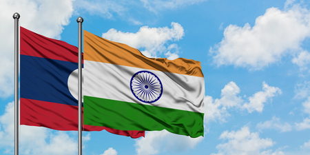 Laos and India flag waving in the wind against white cloudy blue sky together. Diplomacy concept, international relations.