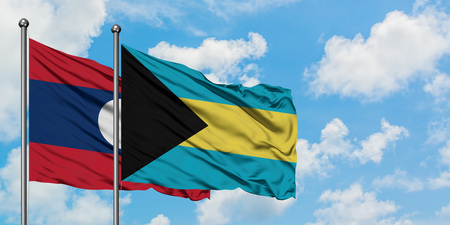 Laos and Bahamas flag waving in the wind against white cloudy blue sky together. Diplomacy concept, international relations. Stock Photo - 123954682