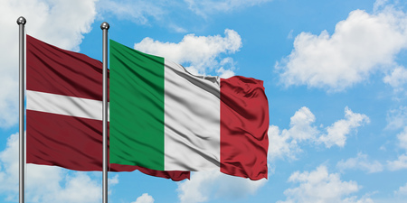 Latvia and Italy flag waving in the wind against white cloudy blue sky together. Diplomacy concept, international relations.