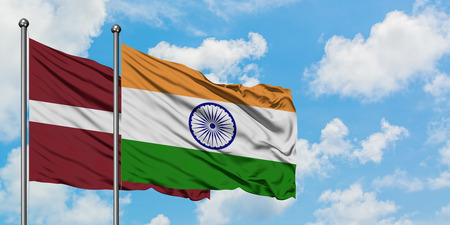 Latvia and India flag waving in the wind against white cloudy blue sky together. Diplomacy concept, international relations.