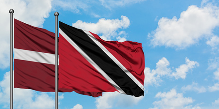 Latvia and Trinidad And Tobago flag waving in the wind against white cloudy blue sky together. Diplomacy concept, international relations.