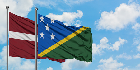 Latvia and Solomon Islands flag waving in the wind against white cloudy blue sky together. Diplomacy concept, international relations.
