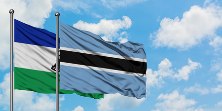Lesotho and Botswana flag waving in the wind against white cloudy blue sky together. Diplomacy concept, international relations.