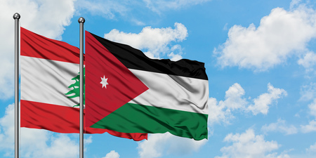 Lebanon and Jordan flag waving in the wind against white cloudy blue sky together. Diplomacy concept, international relations.