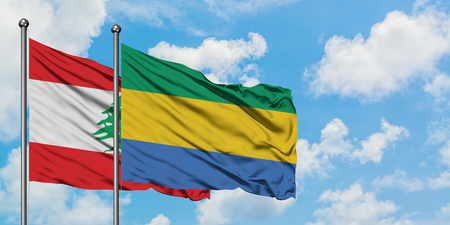 Lebanon and Gabon flag waving in the wind against white cloudy blue sky together. Diplomacy concept, international relations. Фото со стока