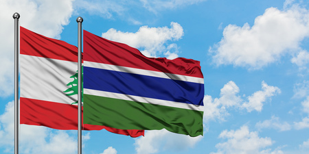 Lebanon and Gambia flag waving in the wind against white cloudy blue sky together. Diplomacy concept, international relations.