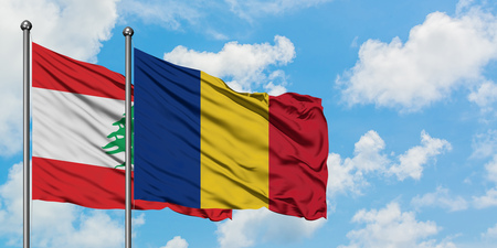 Lebanon and Romania flag waving in the wind against white cloudy blue sky together. Diplomacy concept, international relations.