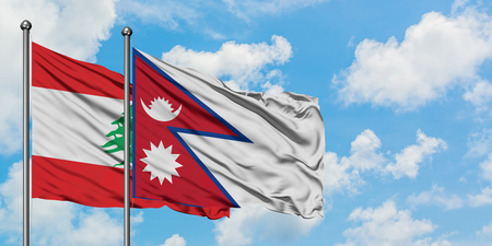 Lebanon and Nepal flag waving in the wind against white cloudy blue sky together. Diplomacy concept, international relations. Banco de Imagens