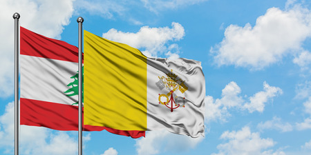 Lebanon and Vatican City flag waving in the wind against white cloudy blue sky together. Diplomacy concept, international relations.