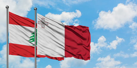 Lebanon and Malta flag waving in the wind against white cloudy blue sky together. Diplomacy concept, international relations. Banco de Imagens
