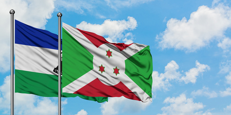 Lesotho and Burundi flag waving in the wind against white cloudy blue sky together. Diplomacy concept, international relations. Banco de Imagens