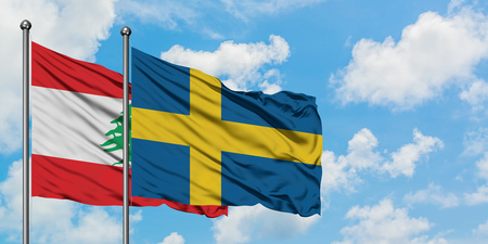 Lebanon and Sweden flag waving in the wind against white cloudy blue sky together. Diplomacy concept, international relations.