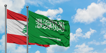 Lebanon and Saudi Arabia flag waving in the wind against white cloudy blue sky together. Diplomacy concept, international relations.