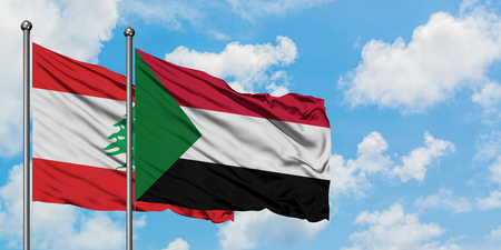 Lebanon and Sudan flag waving in the wind against white cloudy blue sky together. Diplomacy concept, international relations.