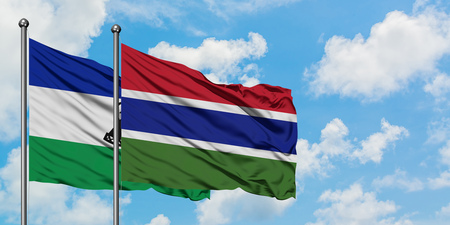 Lesotho and Gambia flag waving in the wind against white cloudy blue sky together. Diplomacy concept, international relations.