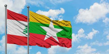 Le Liban et le Myanmar brandissent le drapeau dans le vent contre un ciel bleu nuageux blanc ensemble. Concept de diplomatie, relations internationales.