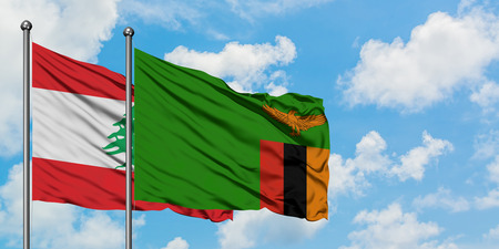 Lebanon and Zambia flag waving in the wind against white cloudy blue sky together. Diplomacy concept, international relations. Banco de Imagens
