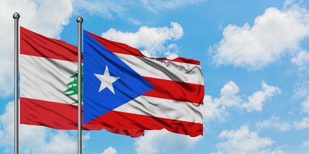 Lebanon and Puerto Rico flag waving in the wind against white cloudy blue sky together. Diplomacy concept, international relations. Banco de Imagens