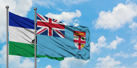 Lesotho and Fiji flag waving in the wind against white cloudy blue sky together. Diplomacy concept, international relations. Banco de Imagens