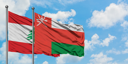 Lebanon and Oman flag waving in the wind against white cloudy blue sky together. Diplomacy concept, international relations. Banco de Imagens
