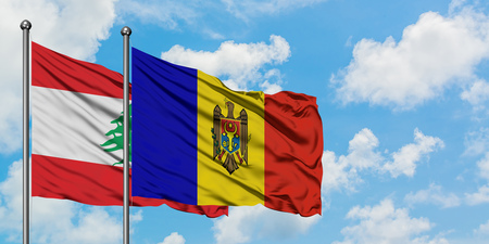 Lebanon and Moldova flag waving in the wind against white cloudy blue sky together. Diplomacy concept, international relations. Banco de Imagens