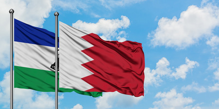 Lesotho and Bahrain flag waving in the wind against white cloudy blue sky together. Diplomacy concept, international relations.