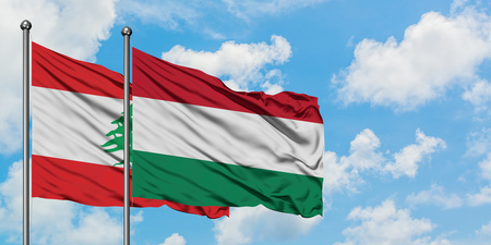 Lebanon and Hungary flag waving in the wind against white cloudy blue sky together. Diplomacy concept, international relations.