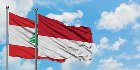 Lebanon and Indonesia flag waving in the wind against white cloudy blue sky together. Diplomacy concept, international relations. Banco de Imagens