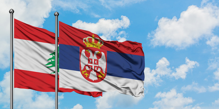 Lebanon and Serbia flag waving in the wind against white cloudy blue sky together. Diplomacy concept, international relations.