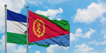 Lesotho and Eritrea flag waving in the wind against white cloudy blue sky together. Diplomacy concept, international relations. Banco de Imagens