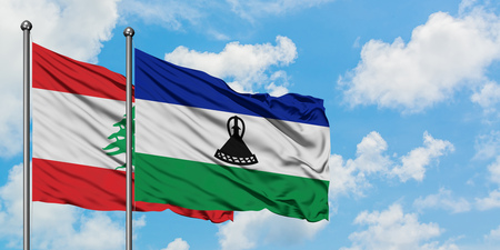 Lebanon and Lesotho flag waving in the wind against white cloudy blue sky together. Diplomacy concept, international relations. Banco de Imagens