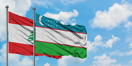 Lebanon and Uzbekistan flag waving in the wind against white cloudy blue sky together. Diplomacy concept, international relations. Banco de Imagens