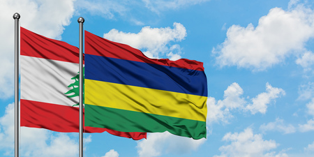 Lebanon and Mauritius flag waving in the wind against white cloudy blue sky together. Diplomacy concept, international relations.