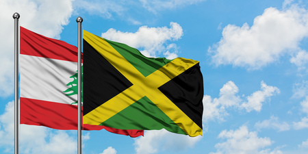 Lebanon and Jamaica flag waving in the wind against white cloudy blue sky together. Diplomacy concept, international relations.