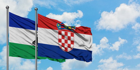 Lesotho and Croatia flag waving in the wind against white cloudy blue sky together. Diplomacy concept, international relations.