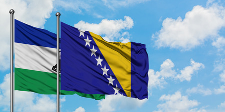 Lesotho and Bosnia Herzegovina flag waving in the wind against white cloudy blue sky together. Diplomacy concept, international relations.