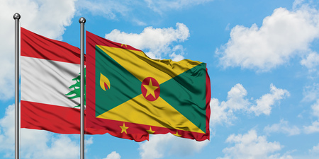 Lebanon and Grenada flag waving in the wind against white cloudy blue sky together. Diplomacy concept, international relations.